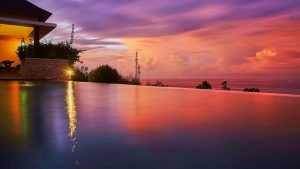 SUNSET ACROSS INFINITY POOL AT VILLA 353 DEGREES NORTH ON NUSA LEMBONGAN, BALI